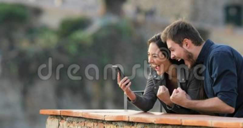 Excited couple checking phone content in a balcony. Excited couple checking smart phone content in a rural apartment balcony stock video footage
