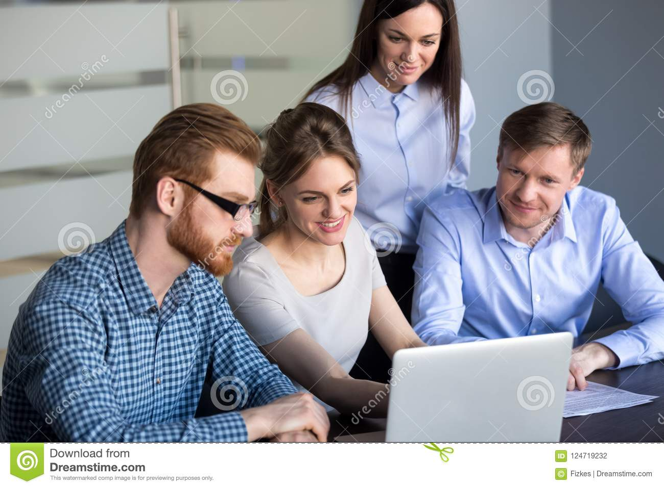 Excited employees looking at laptop observing growing statistics