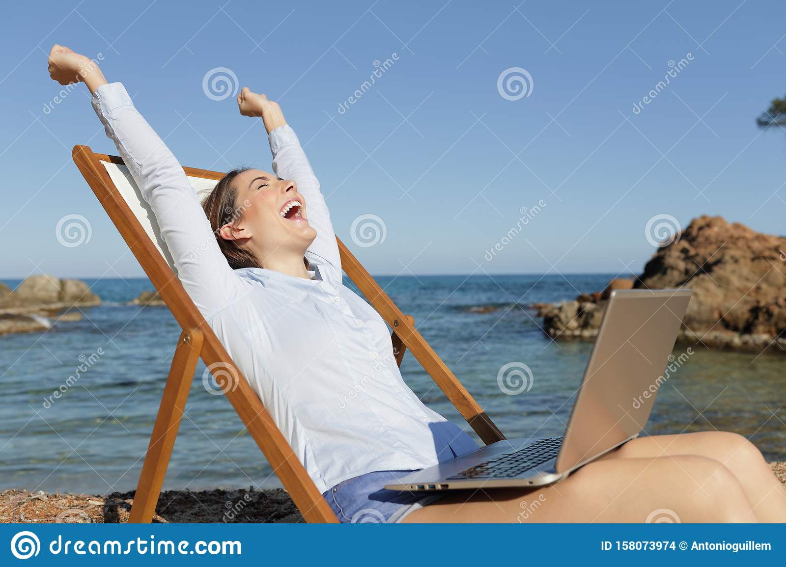 Excited entrepreneur with laptop celebrating success
