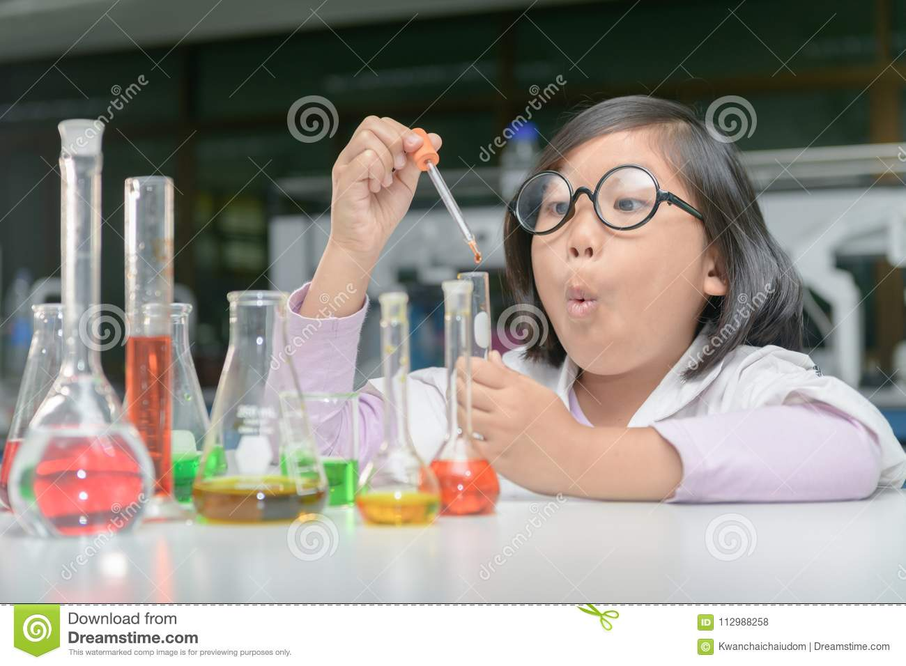 Excited girl making experiment with test tube