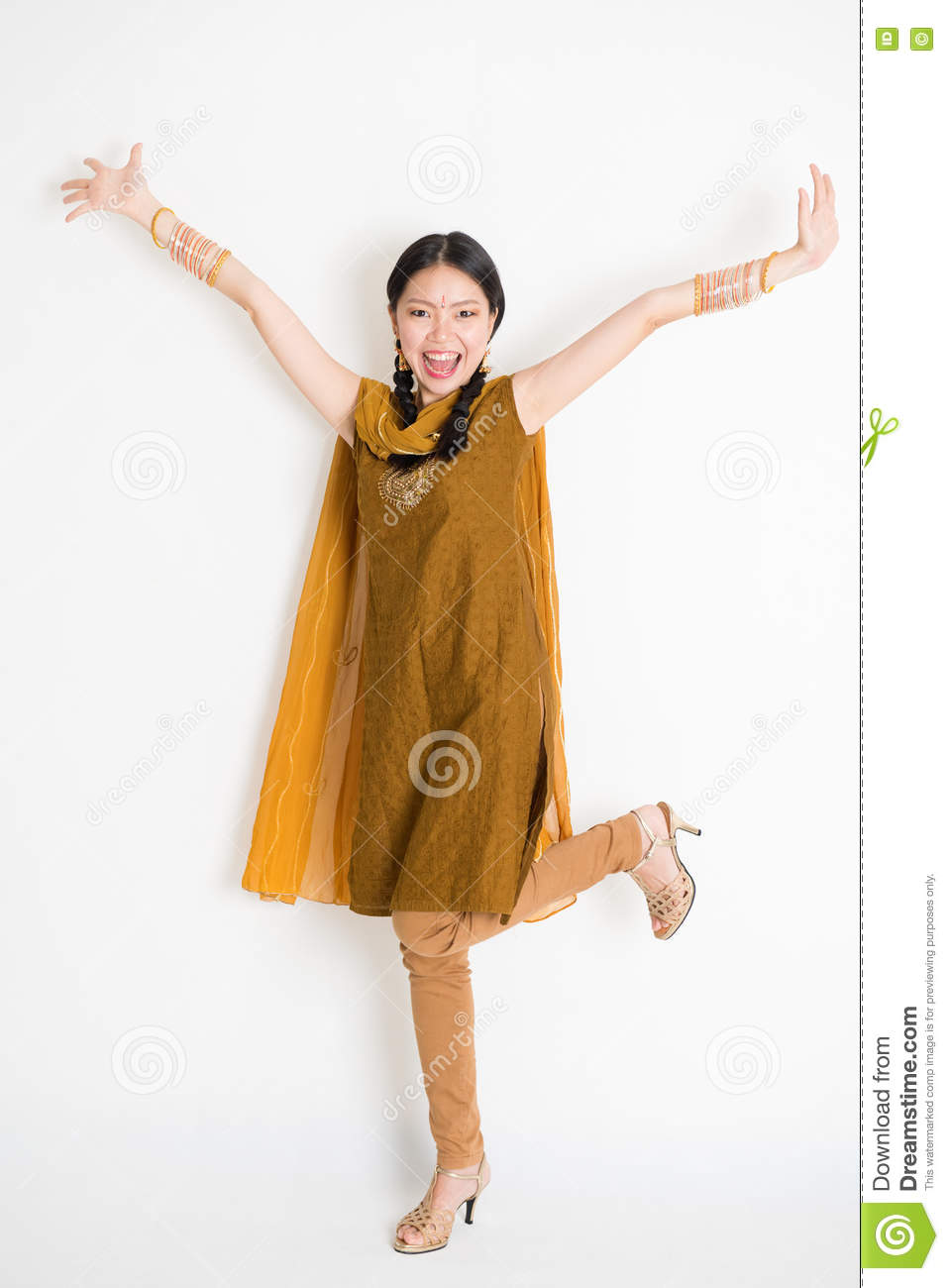 0d27f9a883 Portrait of excited mixed race Indian Chinese girl in traditional punjabi  dress arms raised, full length standing on plain white background.