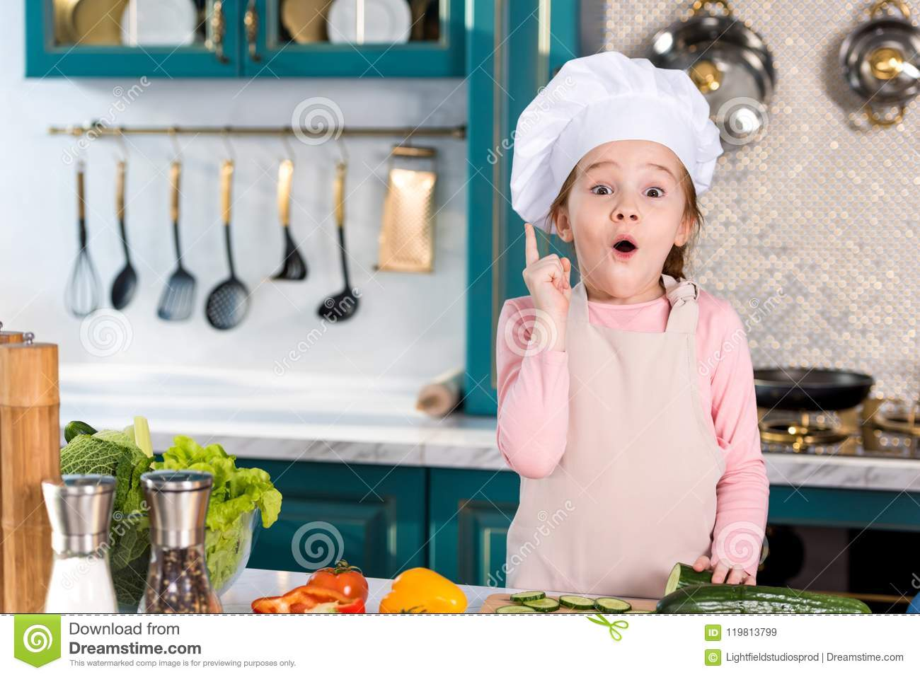 Excited Little Child In Chef Hat And Apron Pointing Up With Finger