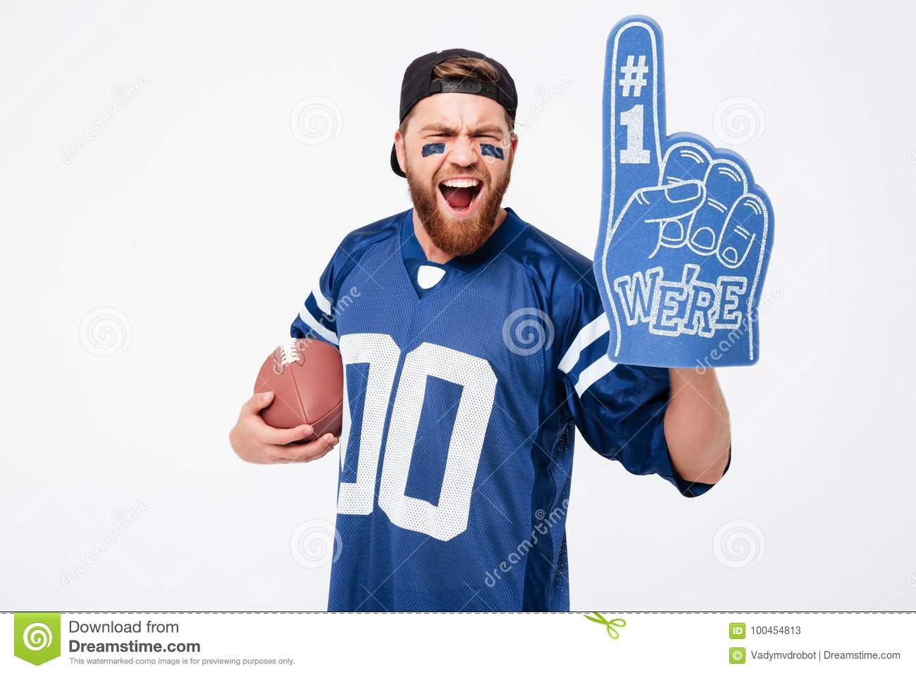 Excited man fan wearing fan glove holding rugby ball.