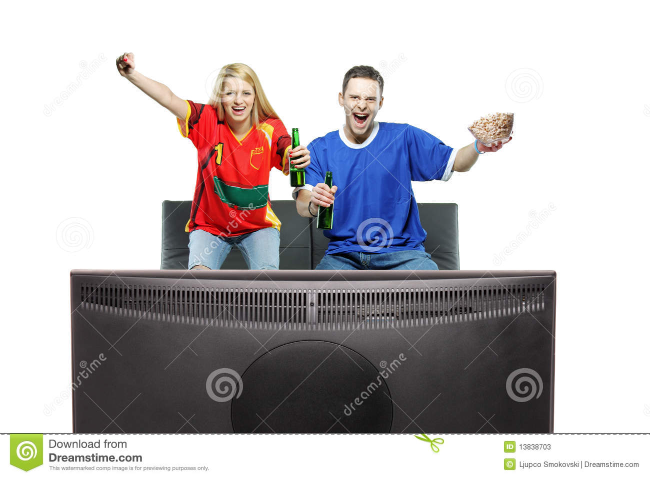 Excited man and woman watching sport on a TV