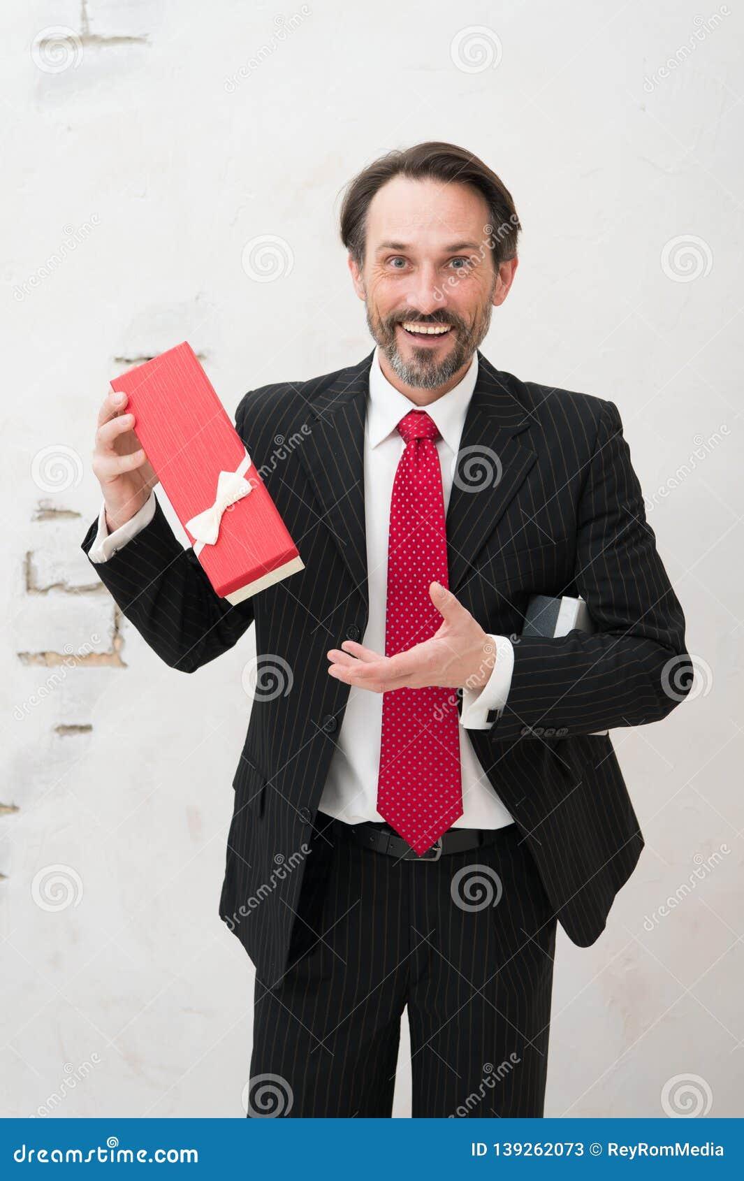 Excited mature man in classic suit holding elegant gift box