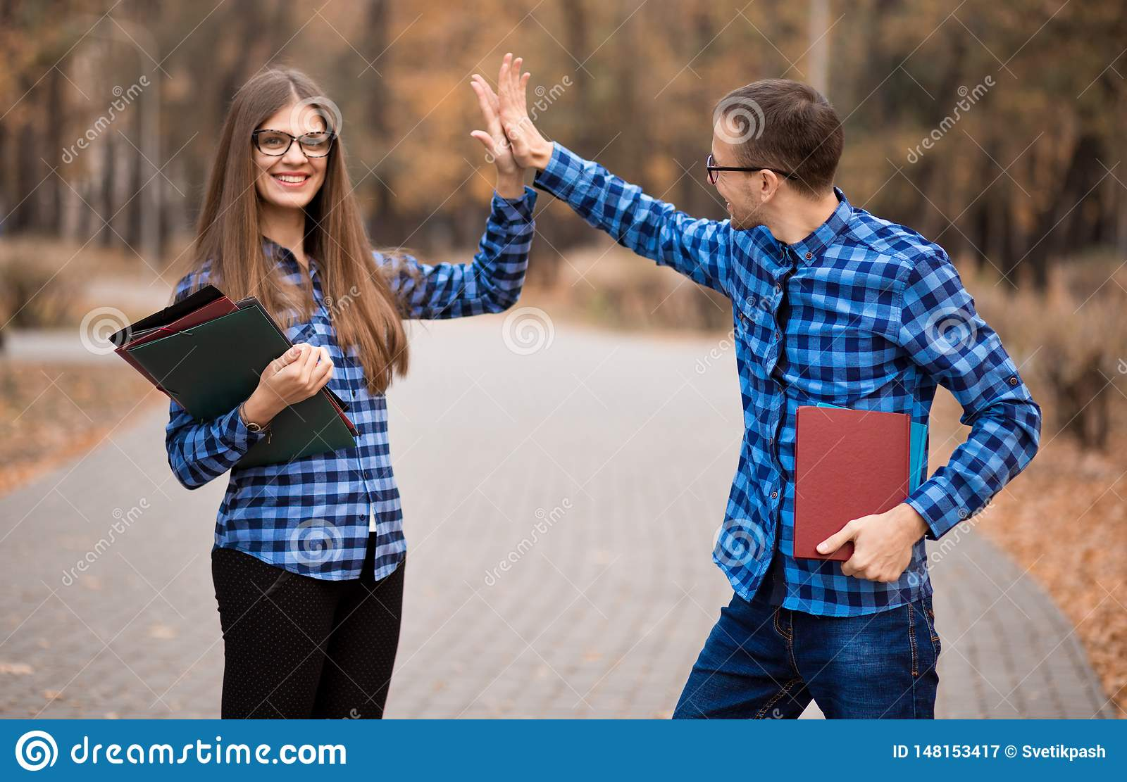 Excited man and woman screaming with joy raising hands, happy young couple celebrate online win victory, goal achievement