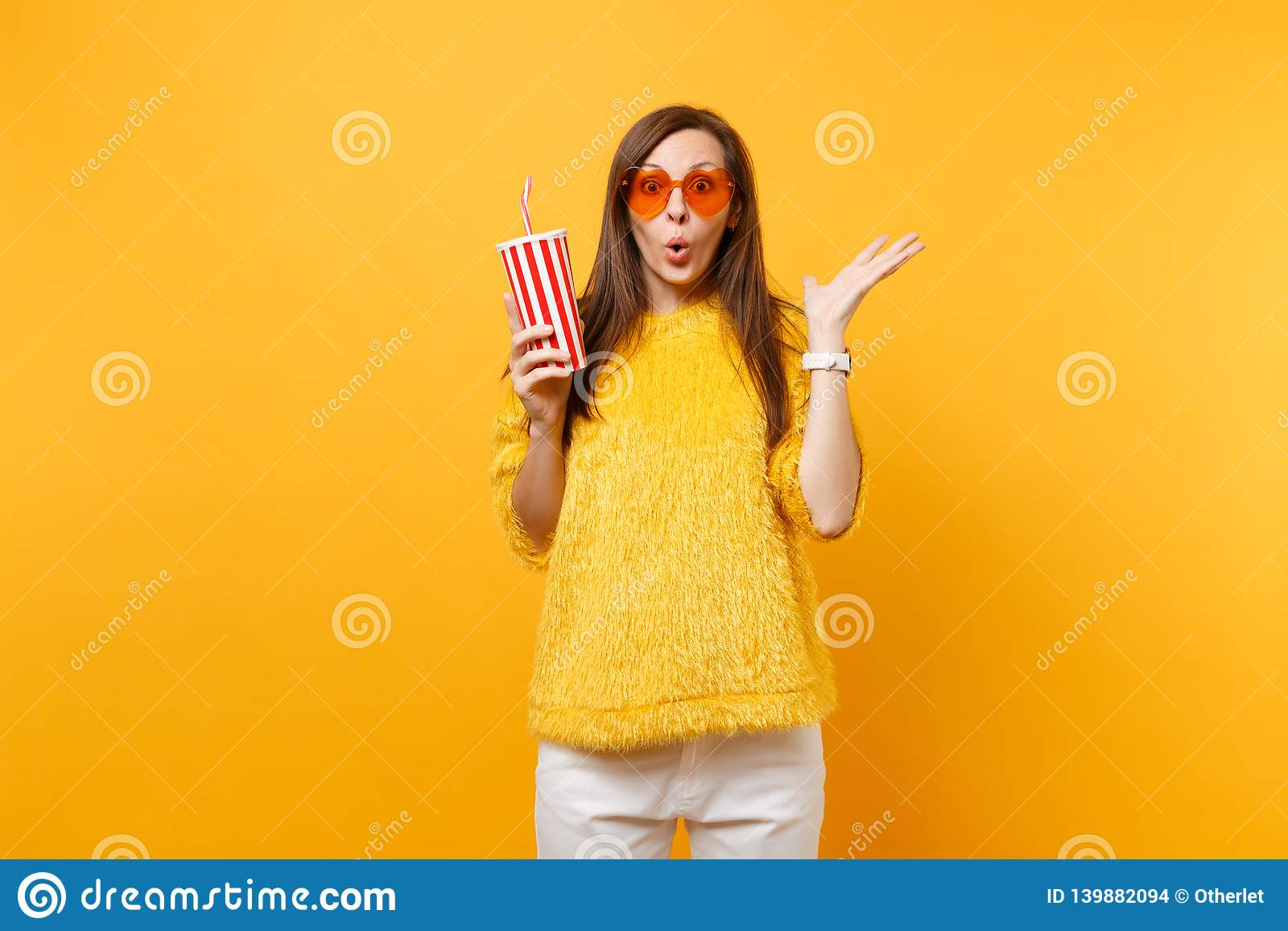 Excited shocked young woman in heart orange glasses spreading hands, holding plastic cup with cola or soda isolated on