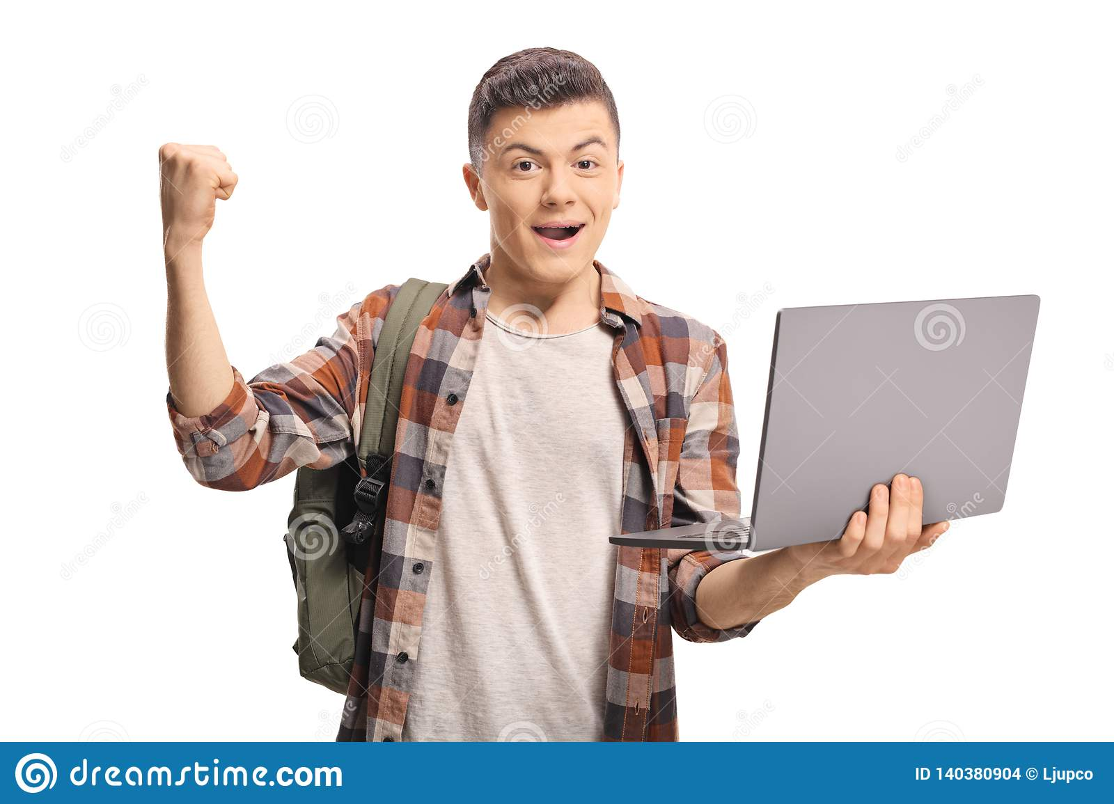 Excited teenage boy holding a laptop and gesturing with hand