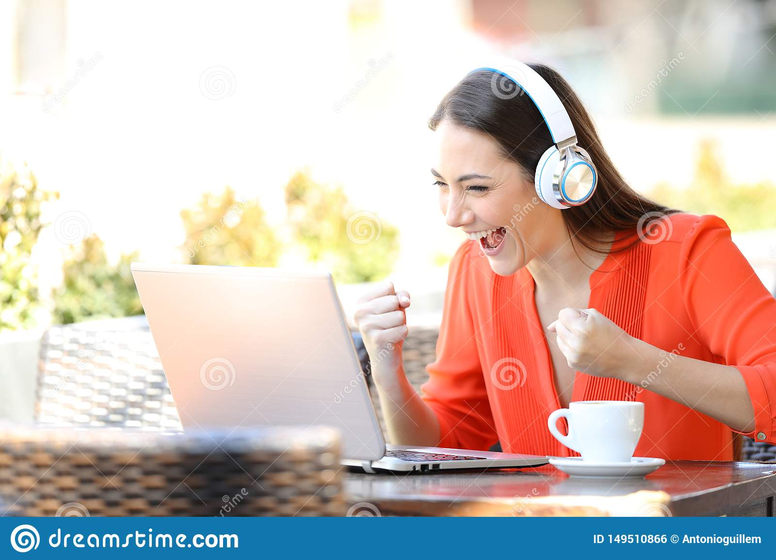 Excited woman watching and listening media on laptop