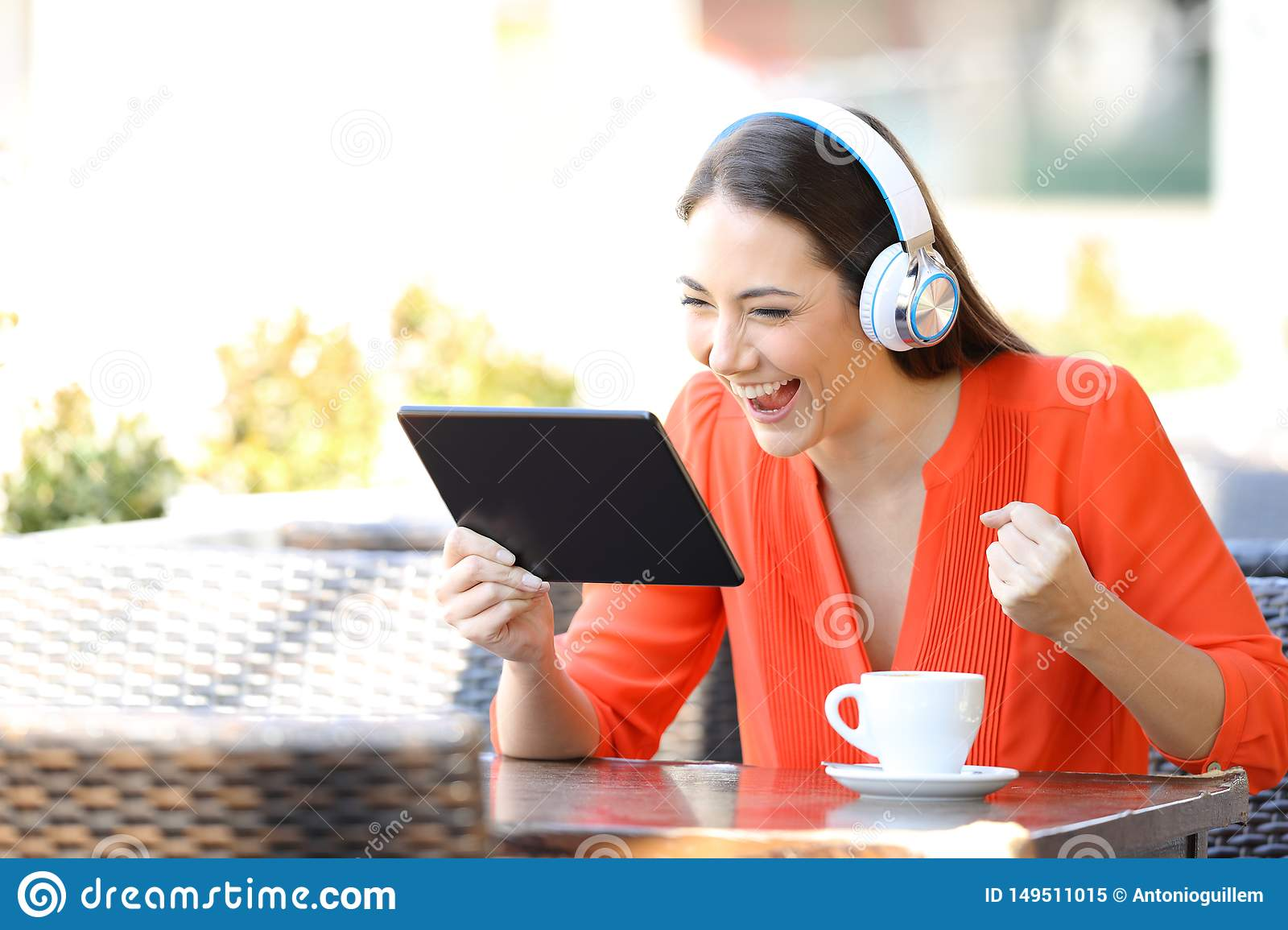 Excited woman watching and listening media on tablet