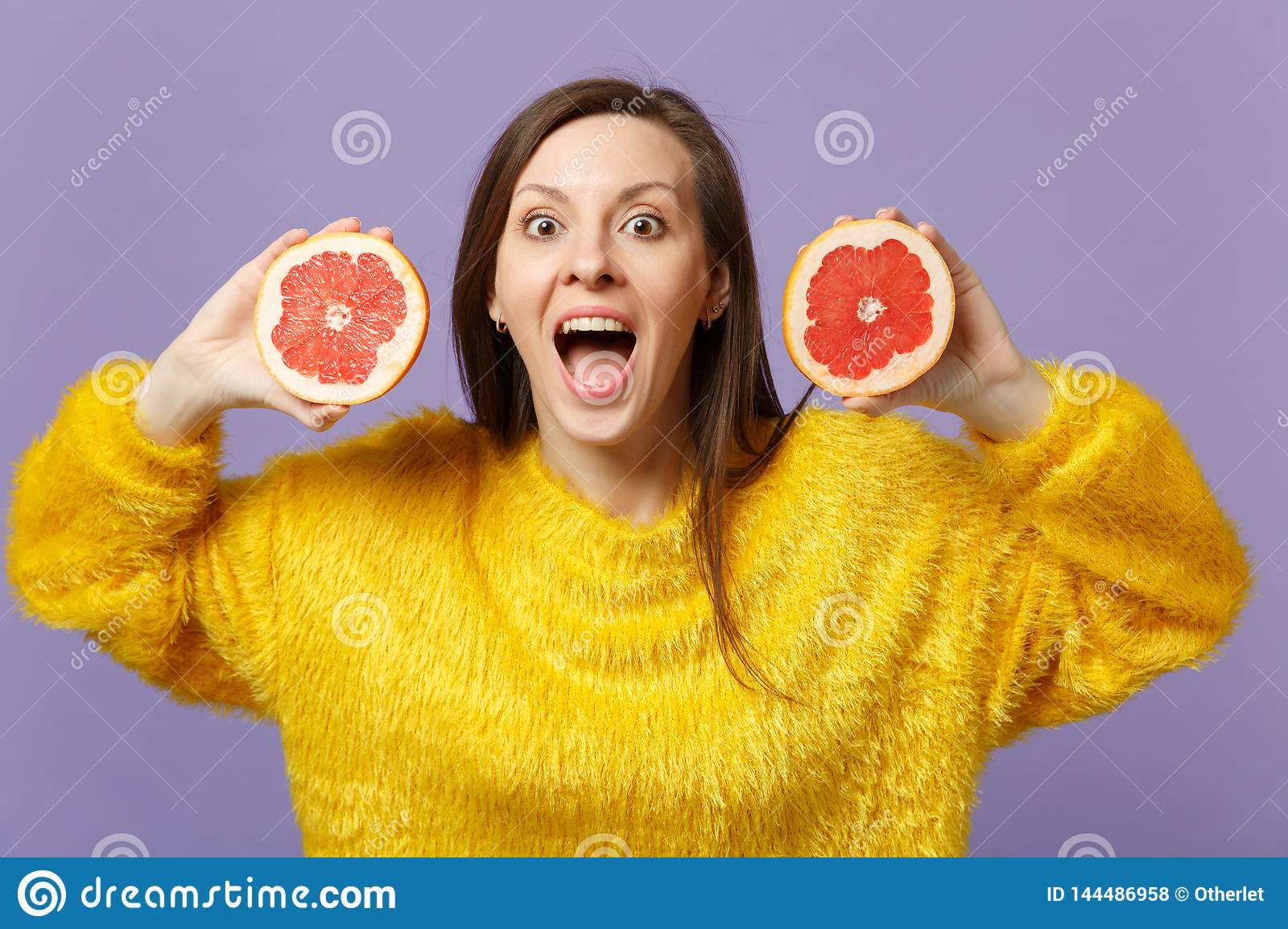 Excited young woman in fur sweater keeping mouth open holding halfs of fresh ripe grapefruit isolated on violet pastel