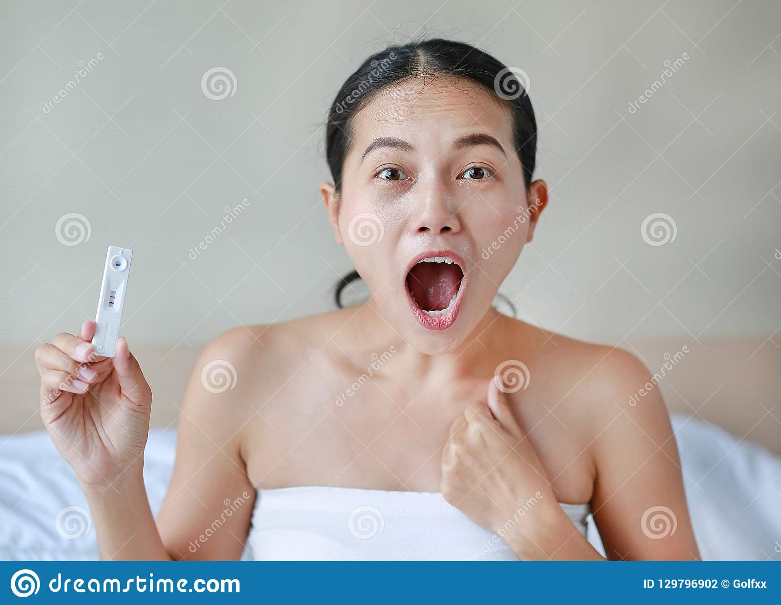 Excited young woman holding positive pregnancy test