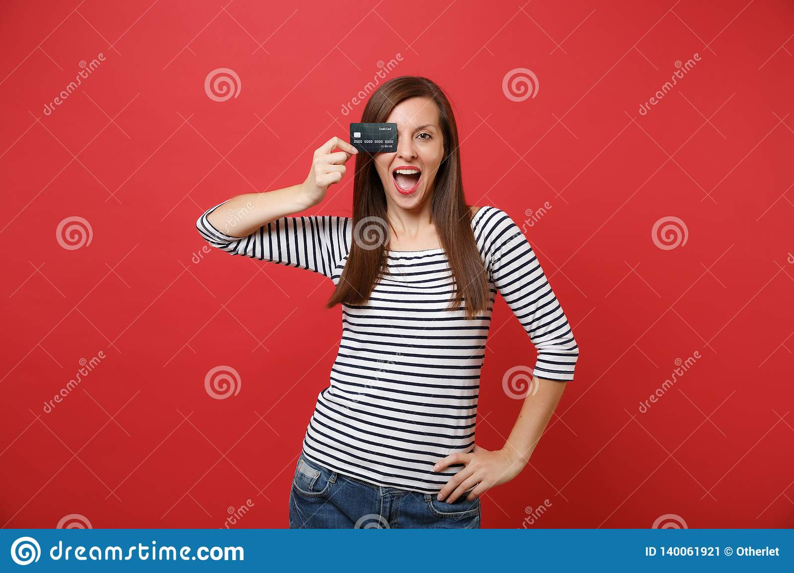 Excited young woman keeping mouth wide open, looking surprised, covering eye with credit card isolated on bright red