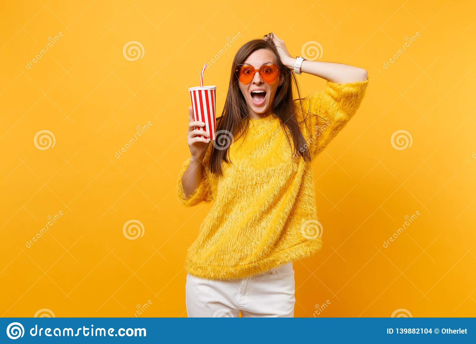 Excited young woman in sweater, heart orange glasses clinging to head holding plastic cup with cola or soda isolated on