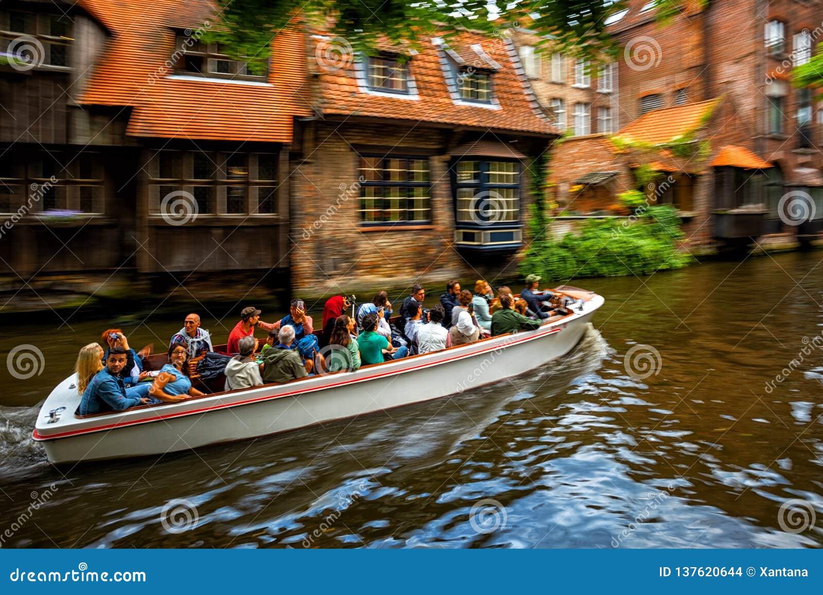 Excursão do barco de canal do turista na cidade velha de Bruges, Bélgica