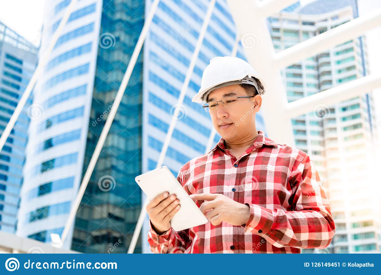 Executive engineer guy is using tablet for record his work or sc