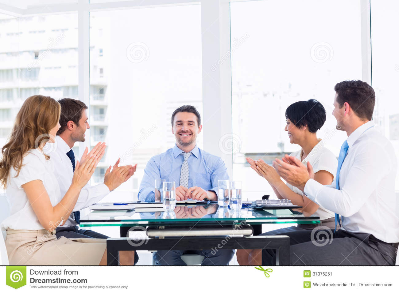 Executives clapping around conference table