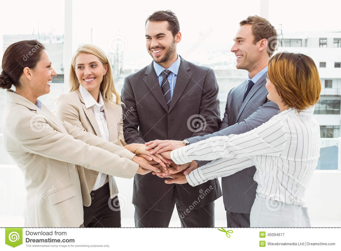 Executives holding hands together in office