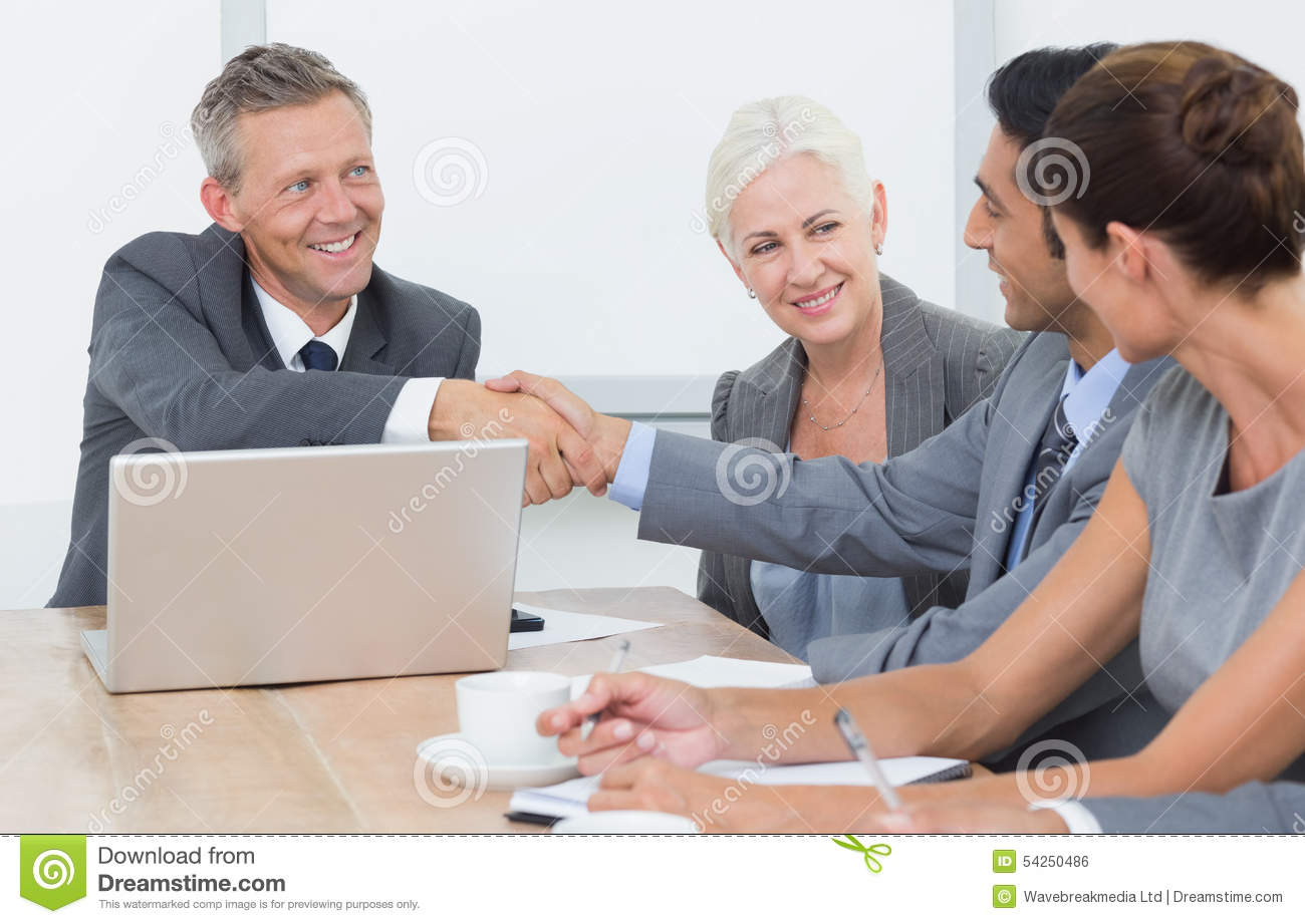 Executives shaking hands in board room meeting