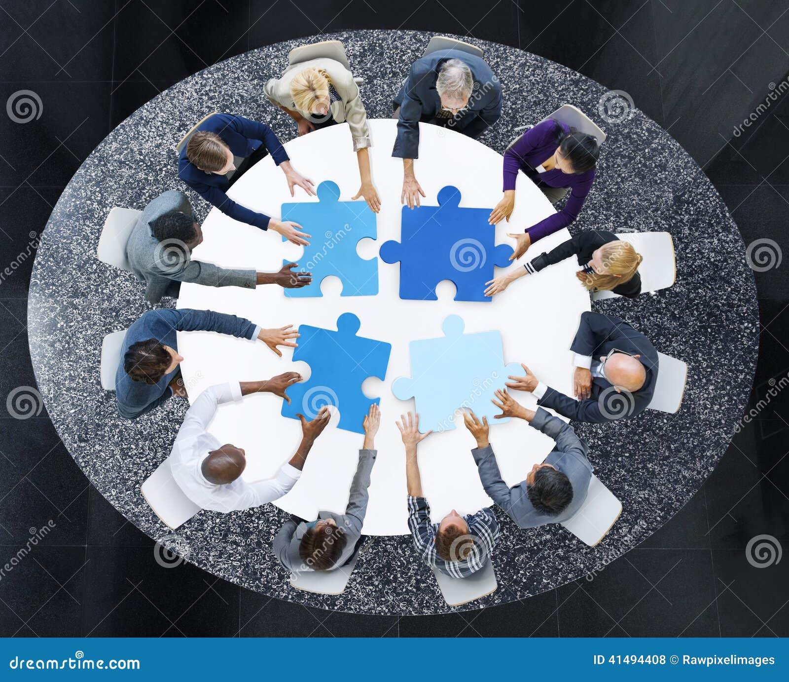 Executivos com partes do enigma e conceito dos trabalhos de equipa