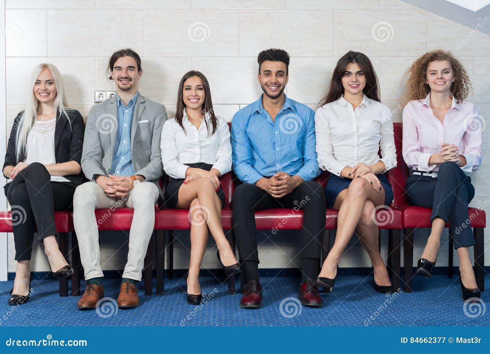 Executivos da reunião de grupo que senta-se na linha fila, recrutamento Job Interview de espera da multidão dos empresários
