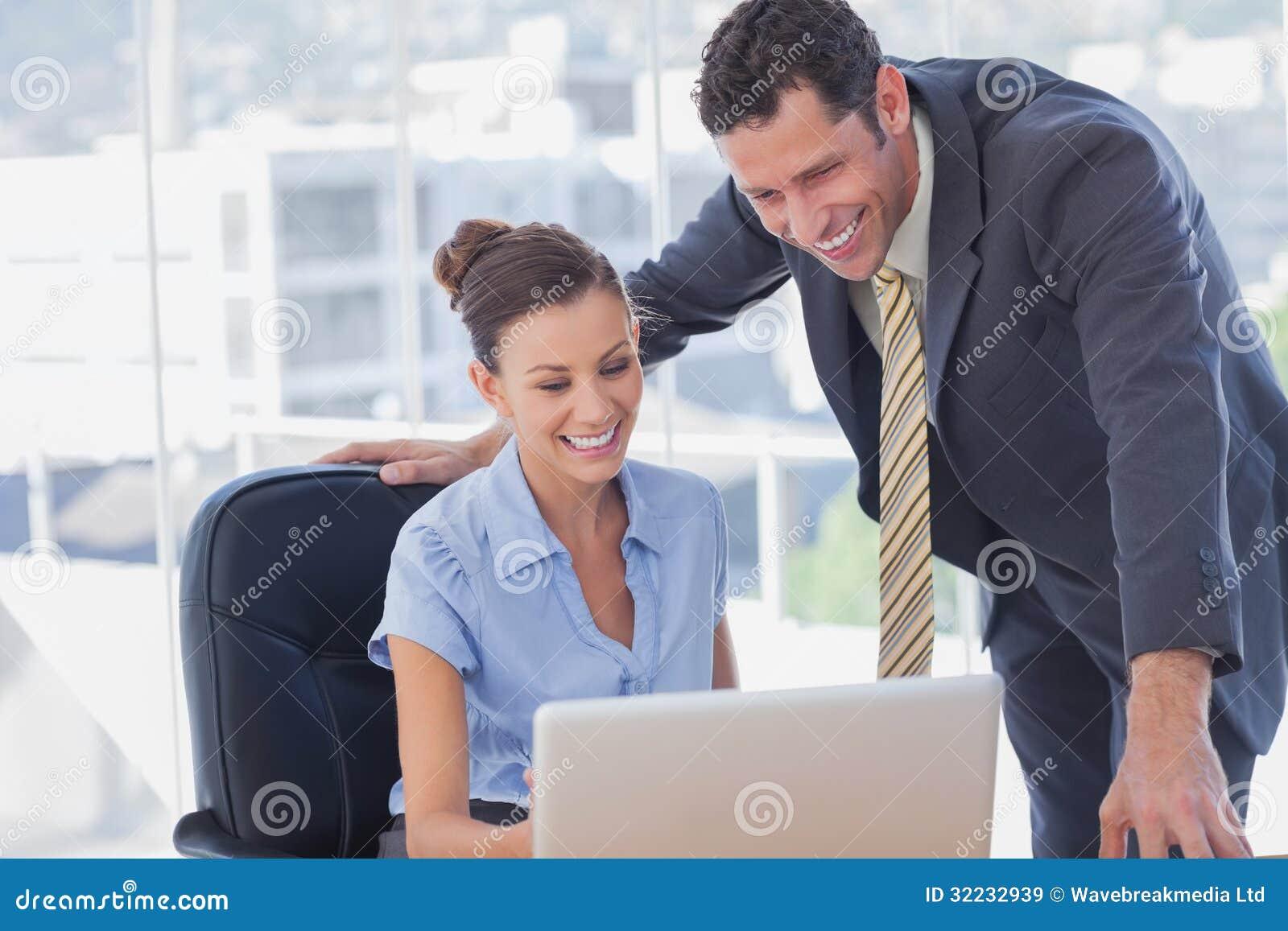 Executivos de sorriso que trabalham junto com o mesmo portátil