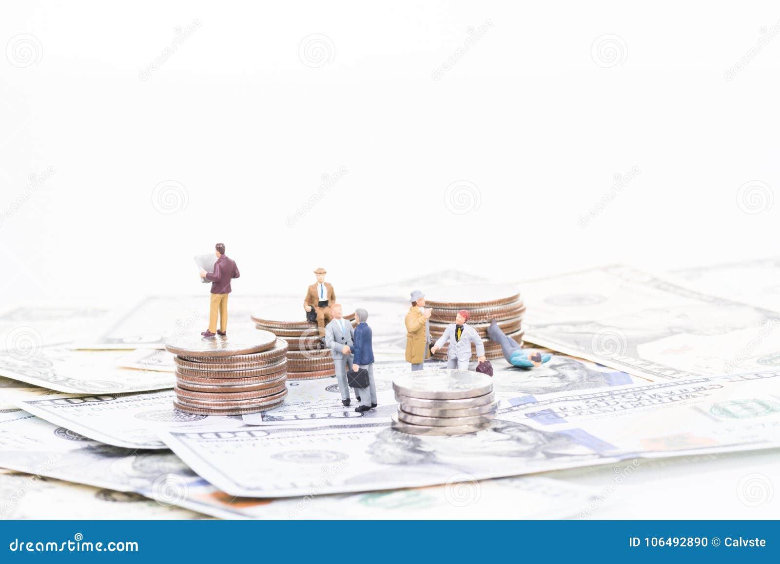 Executivos diminutos em cédulas e em moedas dos E.U.