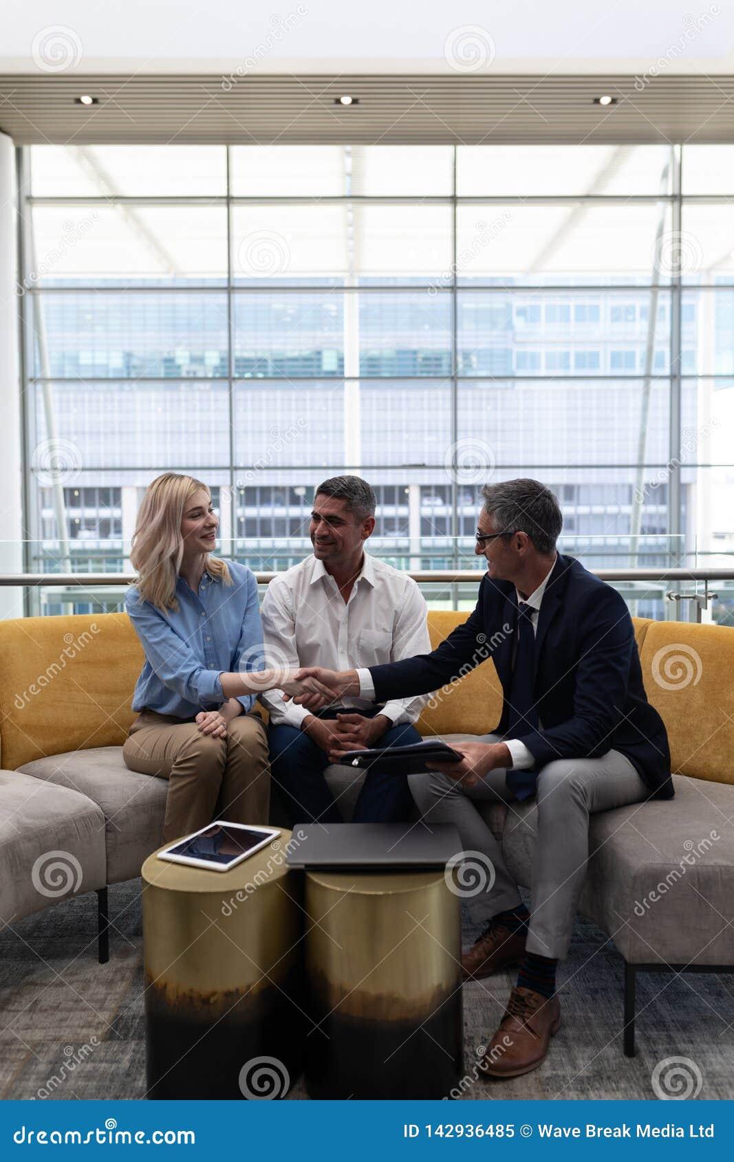 Executivos empresariais dos Caucasians que agitam a mão ao sentar-se no sofá
