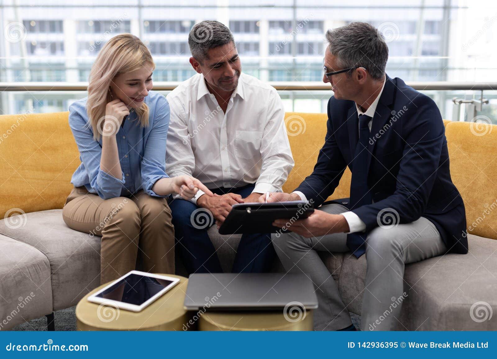 Executivos empresariais dos Caucasians que discutem sobre a tabuleta digital no sofá