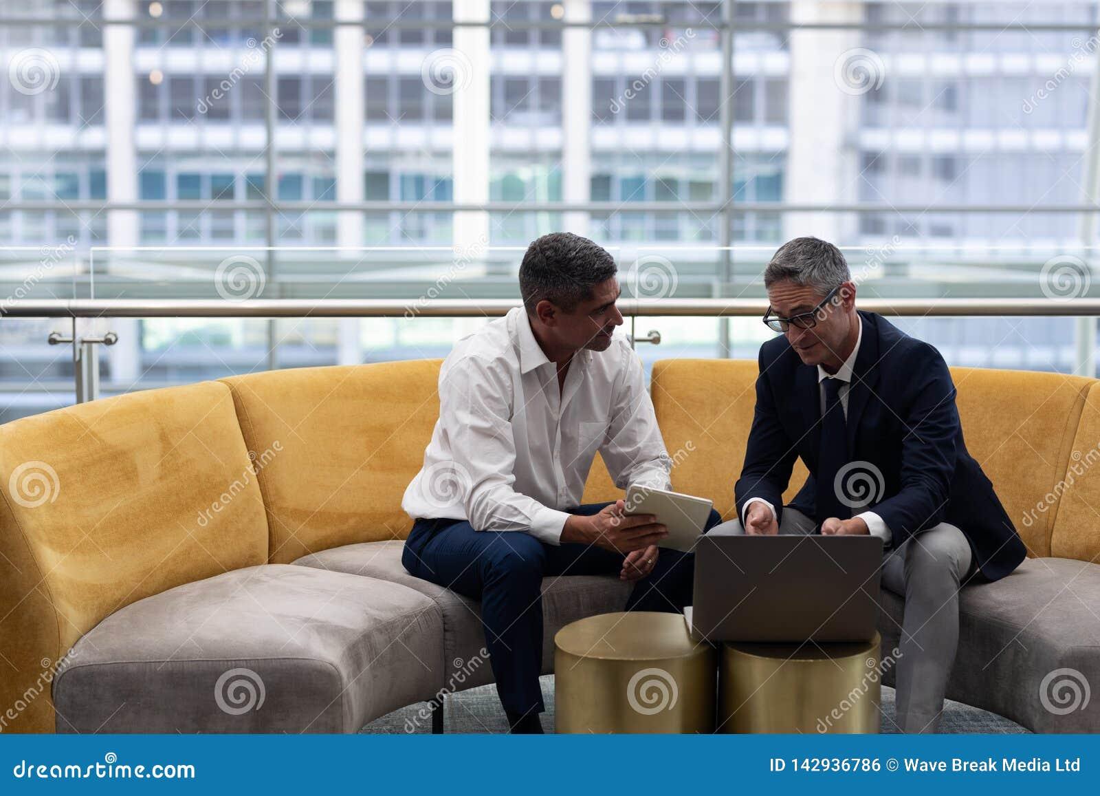 Executivos empresariais dos Caucasians que falam a discussão sobre o portátil ao sentar-se no sofá