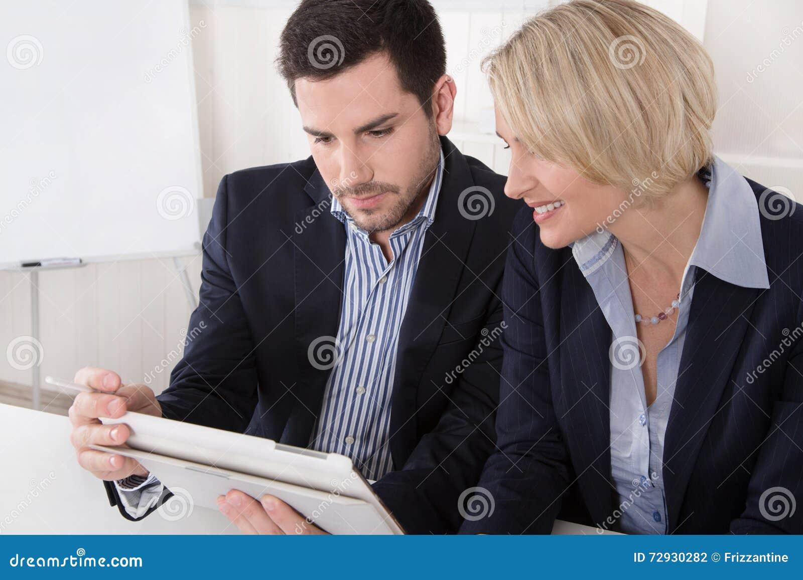 Executivos masculinos e fêmeas que olham uma tela de uma tabuleta