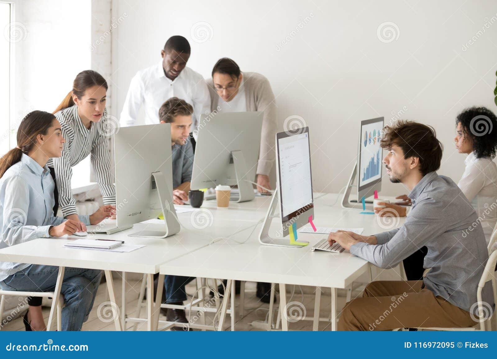 Executivos multirraciais focalizados que trabalham em linha em computadores