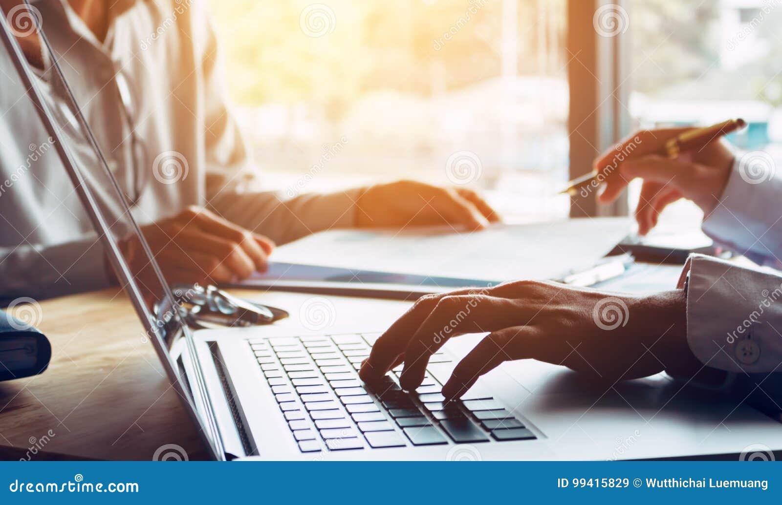 Executivos ou doutor que falam ao cliente e que usam o portátil a