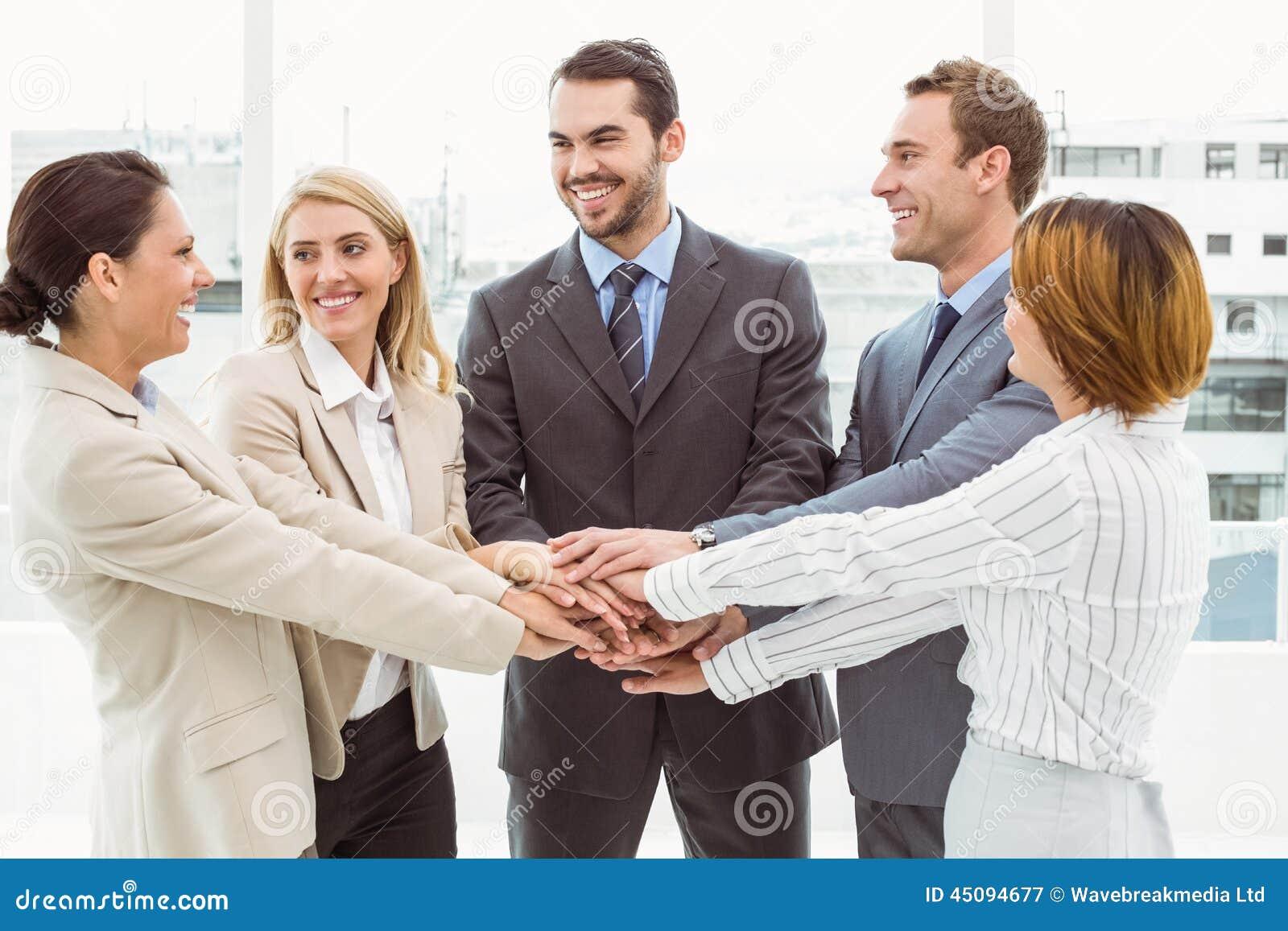 Executivos que mantêm as mãos unidas no escritório