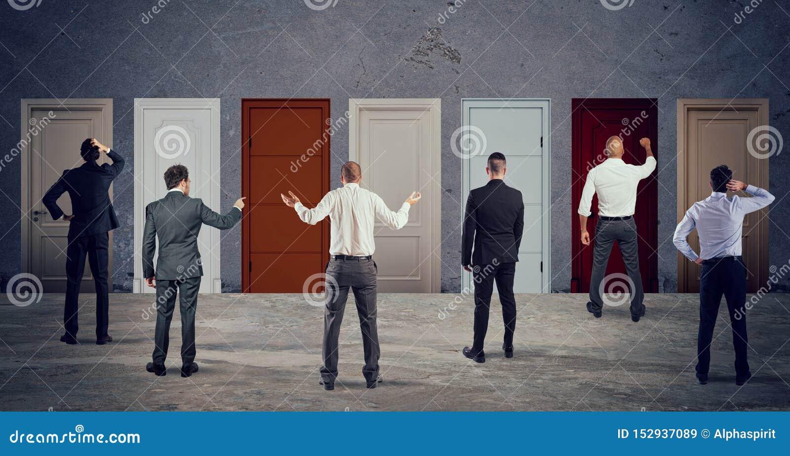 Executivos que olham para selecionar a porta direita Conceito da confusão e da competição