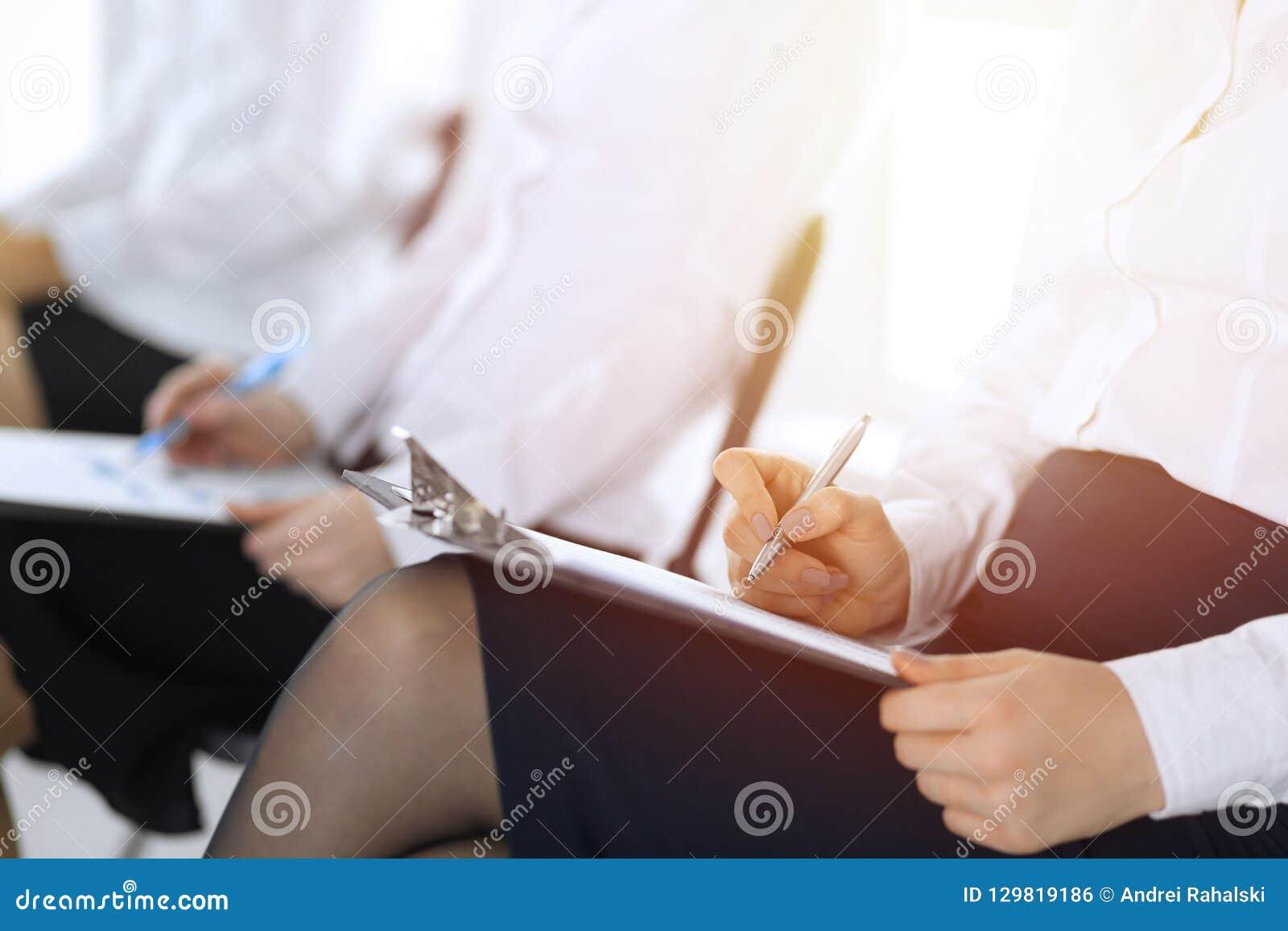 Executivos que participam na conferência ou que treinam no escritório, close-up Mulheres que sentam-se em cadeiras e que fazem an