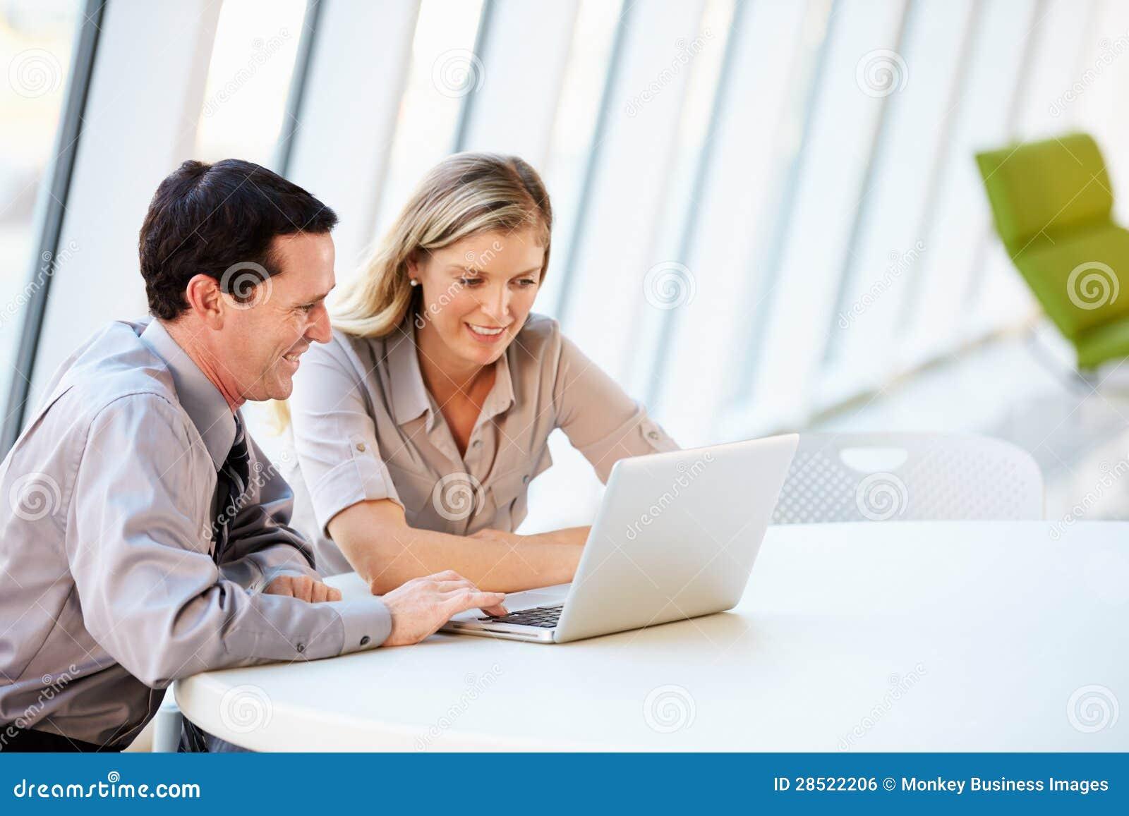 Executivos que têm a reunião em torno da tabela no escritório moderno