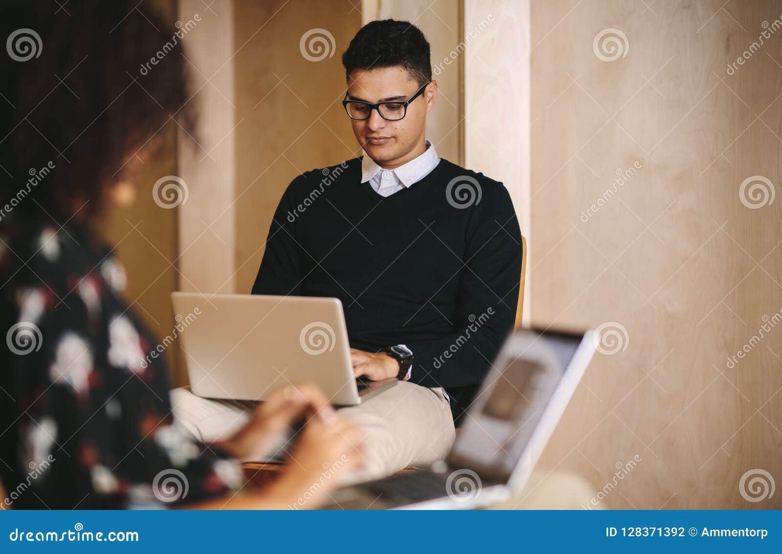 Executivos que trabalham nos laptop que sentam-se em cadeiras