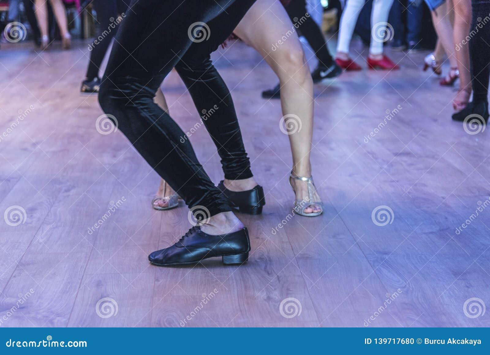 Executores em um salão de baile, interno, pés da dança da salsa dos detalhes, fim acima