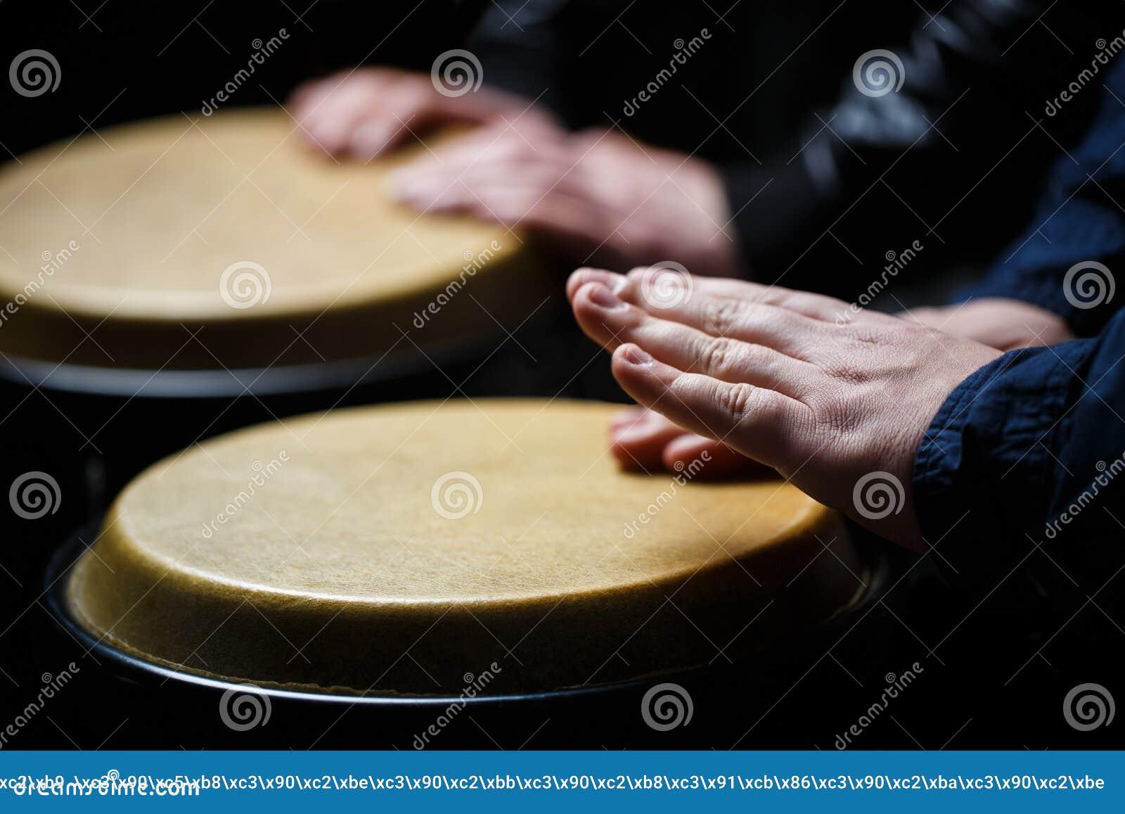 Executores que jogam cilindros de bongos Feche acima da mão do músico que joga cilindros de bongos Cilindro Mãos de um músico que