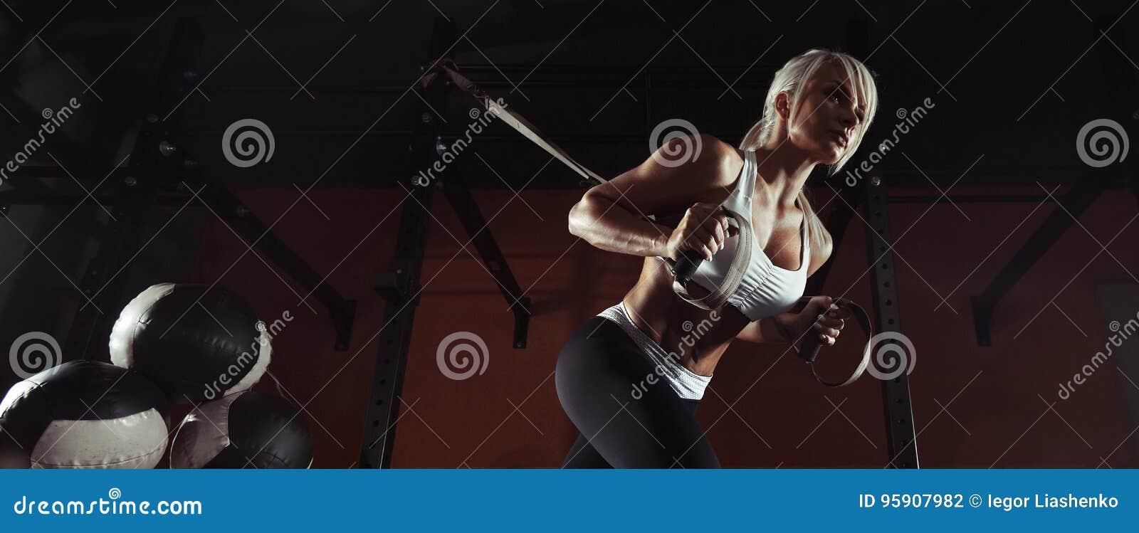 Exercício da mulher da aptidão no TRX no gym