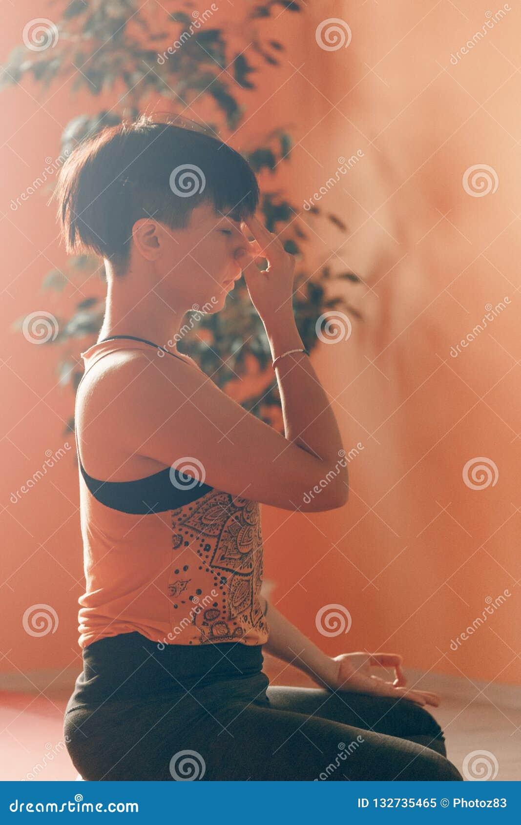 Exercício de respiração praticando da narina alternativa da ioga da jovem mulher