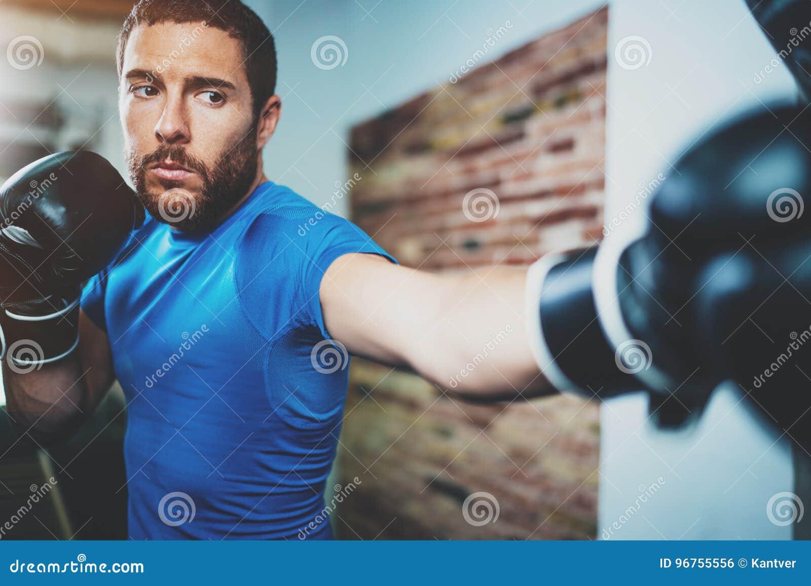 Exercício do encaixotamento do homem novo no gym da aptidão no fundo borrado Homem atlético que treina duramente Conceito do enca