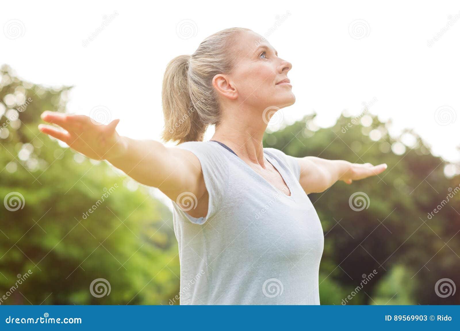 Exercício maduro da ioga da mulher