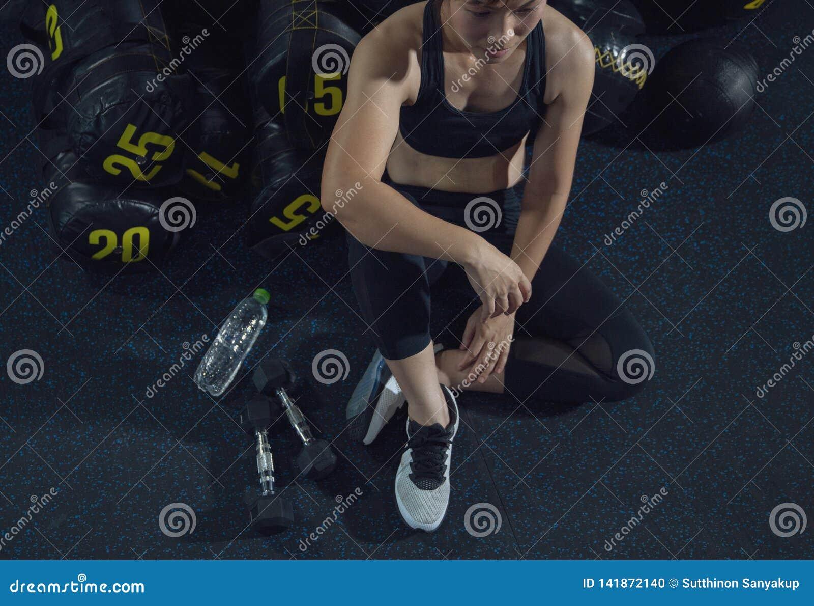 Exerc?cio do exerc?cio da mulher na aptid?o do gym que quebra para relaxar guardando o fruto da ma?? ap?s o esporte de forma??o c