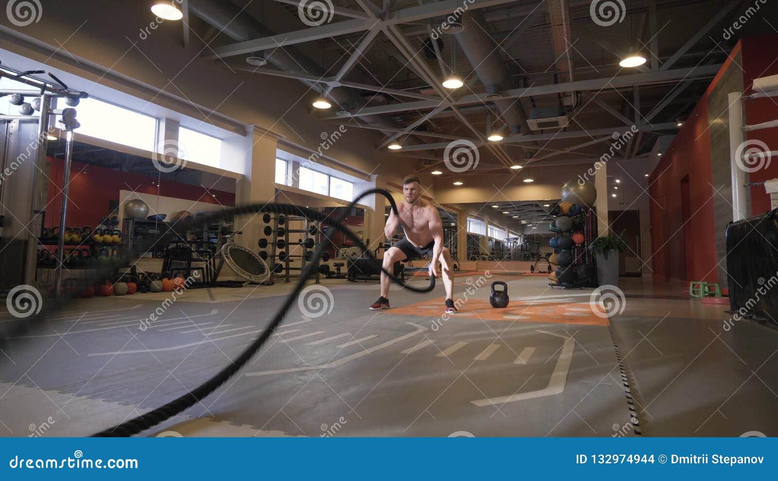 Exercice musculaire de séance d entraînement de formation d homme avec des cordes dans le centre de fitness