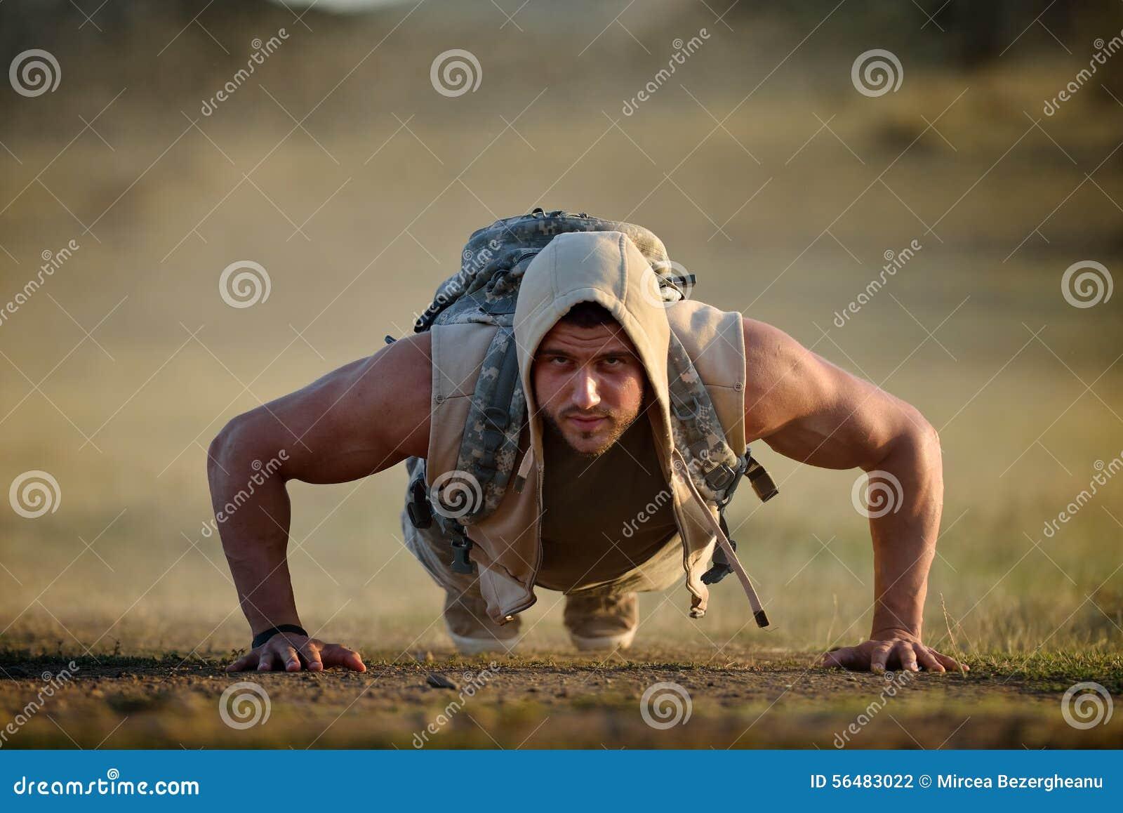 Exercice sportif de jeune homme extérieur sur le champ poussiéreux