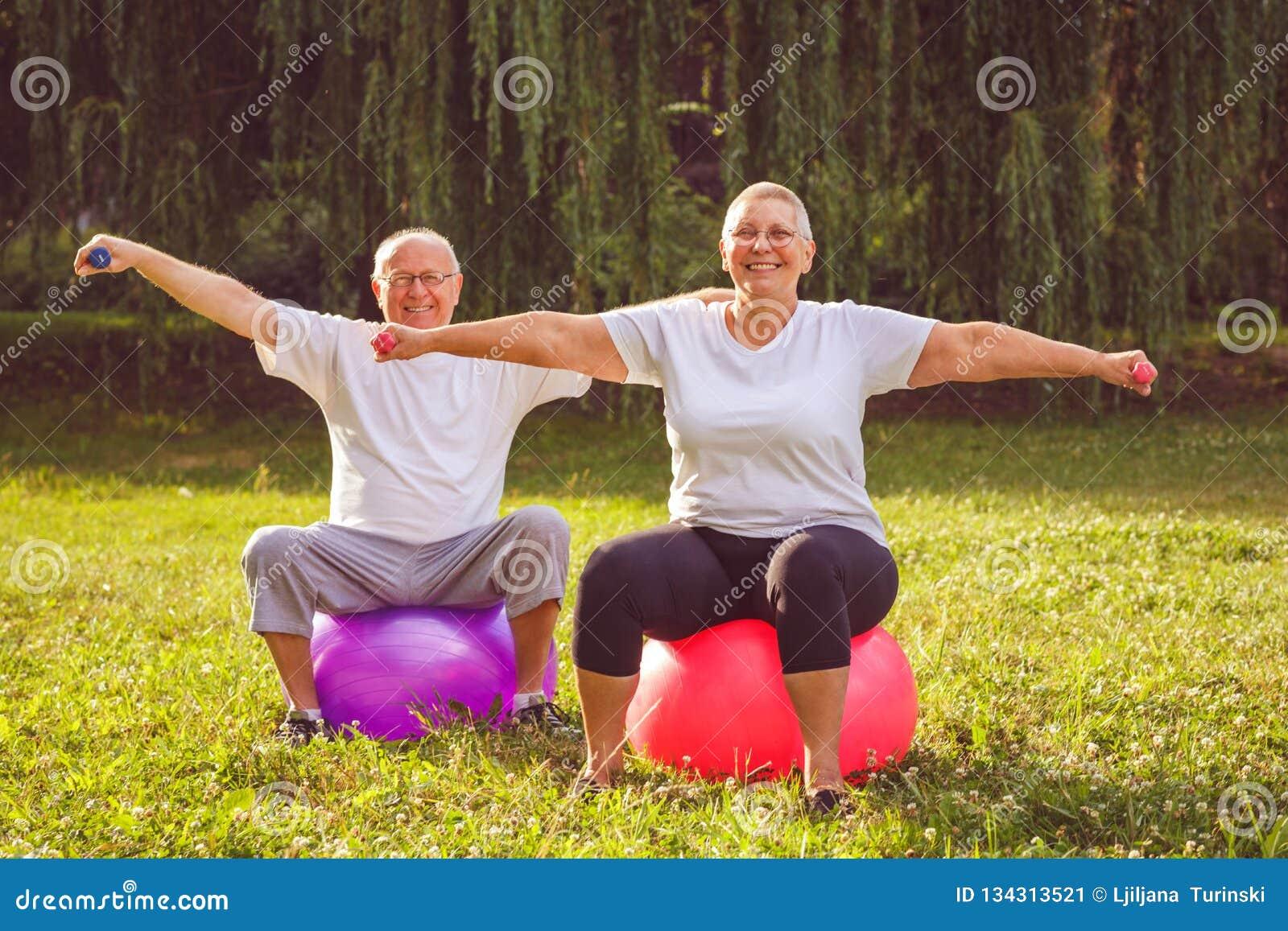 Exercice supérieur - couple de retraité faisant des exercices de forme physique sur la boule de forme physique en parc