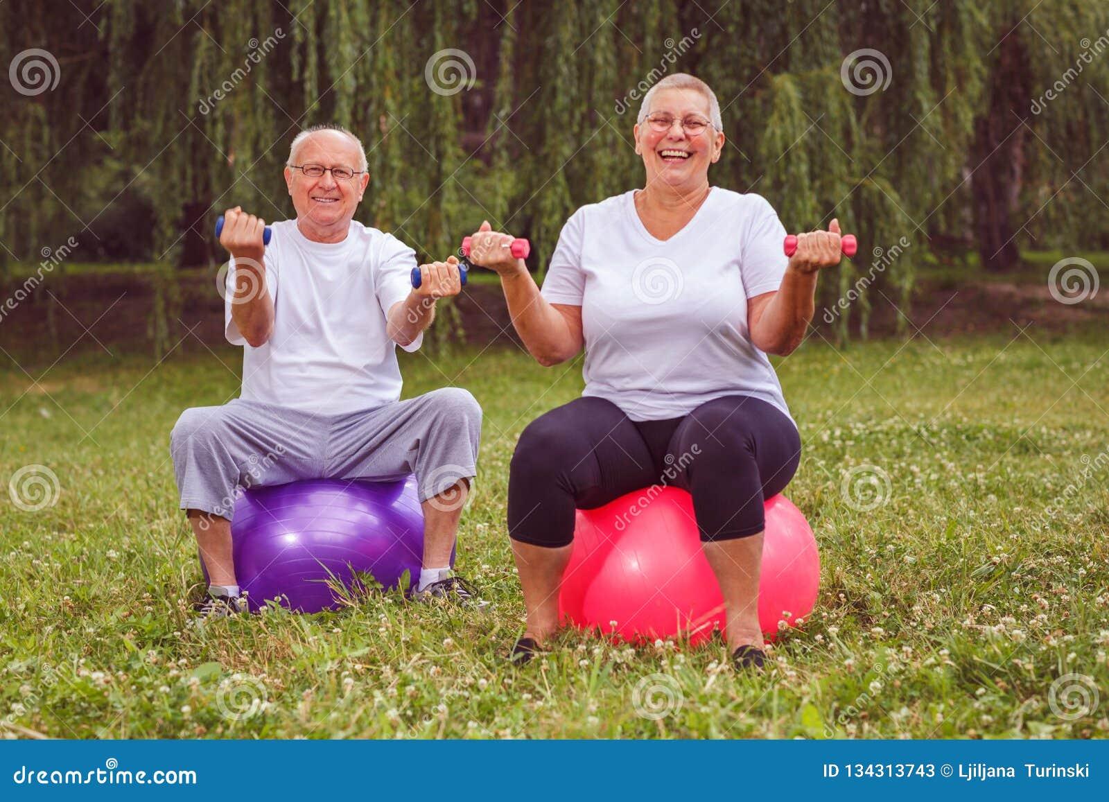 Exercice supérieur - couple de retraité tenant des haltères tout en se reposant sur la boule de forme physique en parc