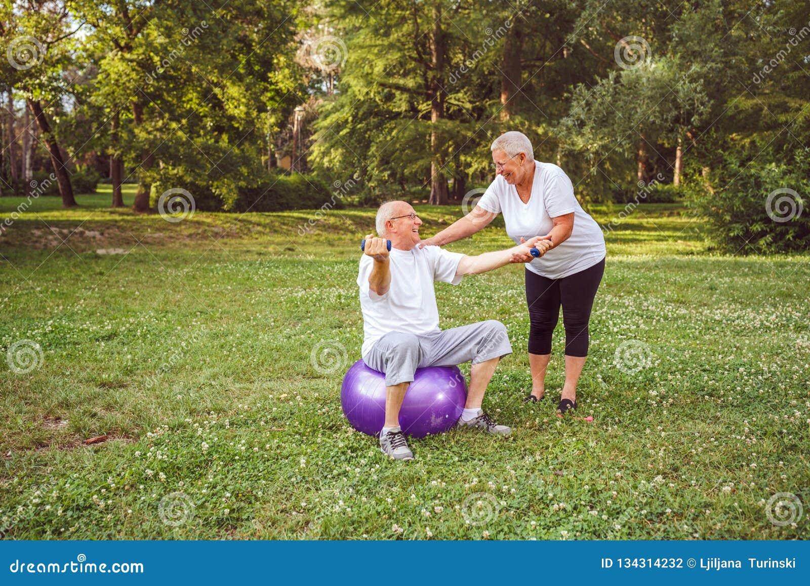 Exercice supérieur - homme mûr et femme faisant ensemble des exercices de forme physique sur la boule de forme physique dans le c
